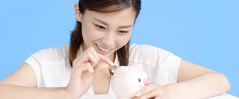 笑顔で貯金をする女性
